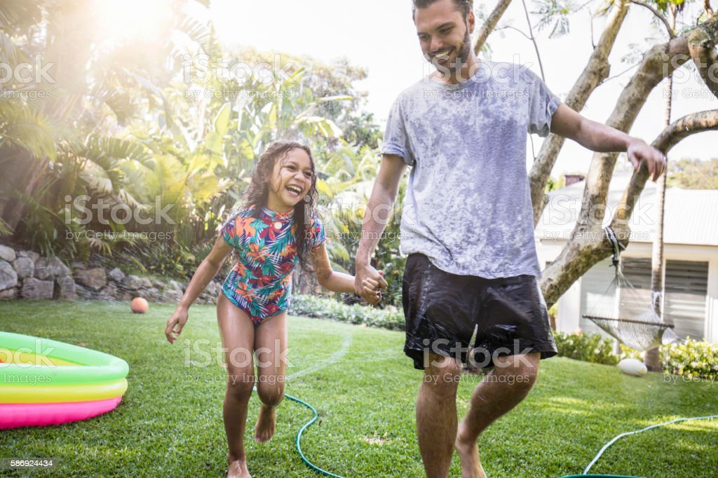Aboriginal father and daughter having fun at backyard garden stock photo