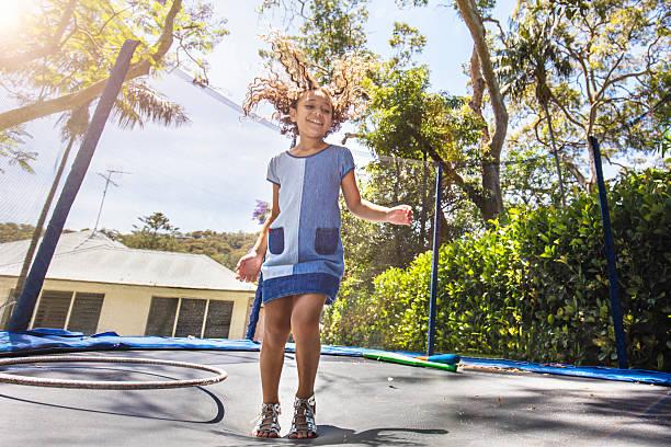 first-nations-mädchen auf und ab springen auf dem trampolin - gartentrampolin stock-fotos und bilder