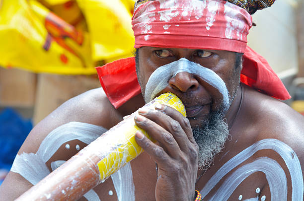 aboriginal indigenous australian man play on didgeridoo in sydney australia - didgeridoo stock photos and pictures