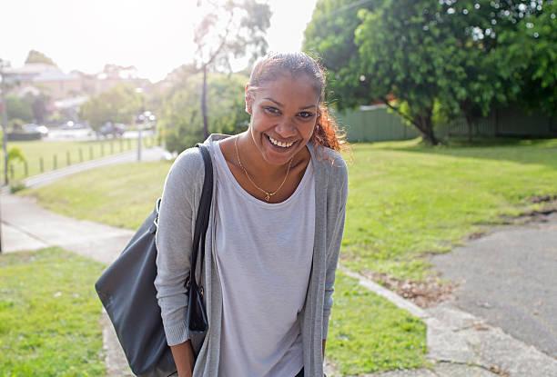 Aboriginal Indigenous woman laughing and walking towards camera stock photo