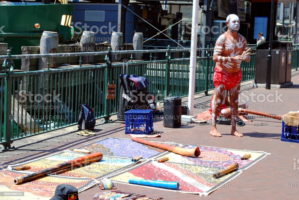 Aboriginal male street busker is giving performance with musical instruments laid out nearby on the ground at Circular Quay stock photo