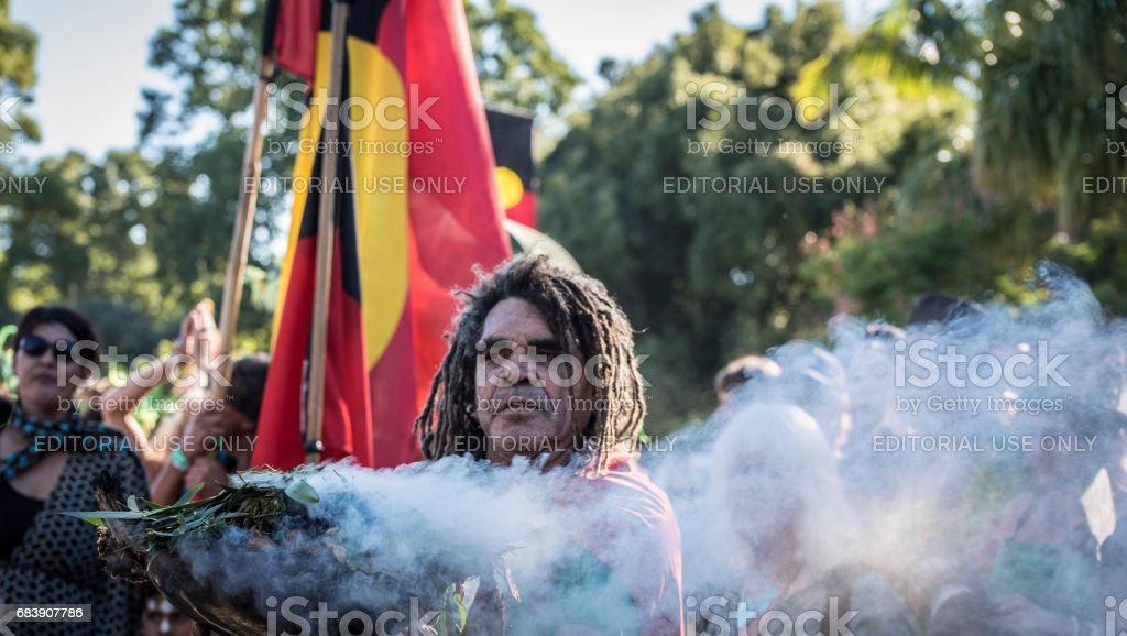 Aboriginal  man conducts a 'smoking ceremony' to lead parade. stock photo