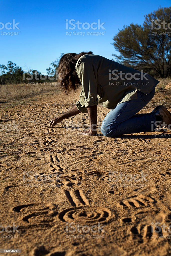 Aboriginal man drawing patterns on the soil stock photo