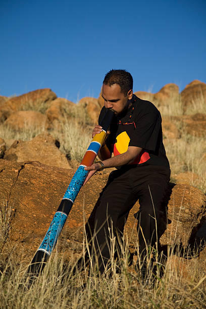 aboriginal man playing the didgeridoo - didgeridoo stock photos and pictures