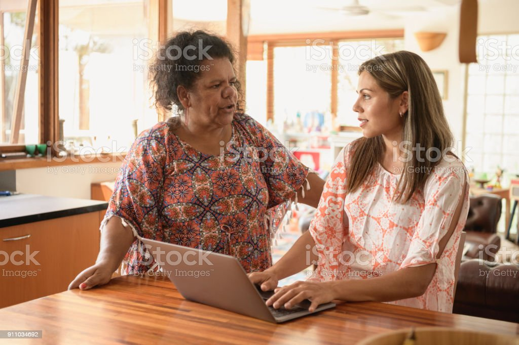 Aboriginal mother talking to daughter working at home on laptop stock photo