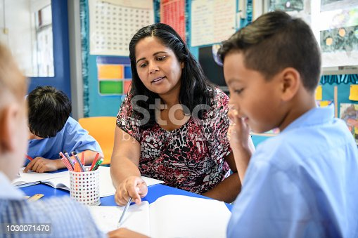 Australian female primary school teacher working with children offering support and guidance