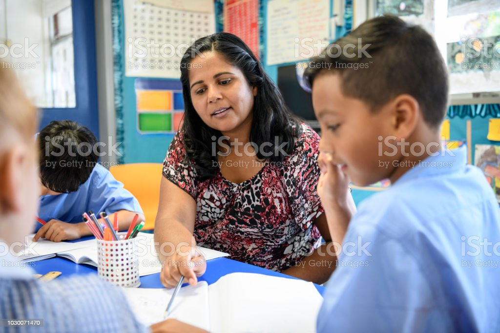 Aboriginal primary school teacher helping young boy in the classroom stock photo