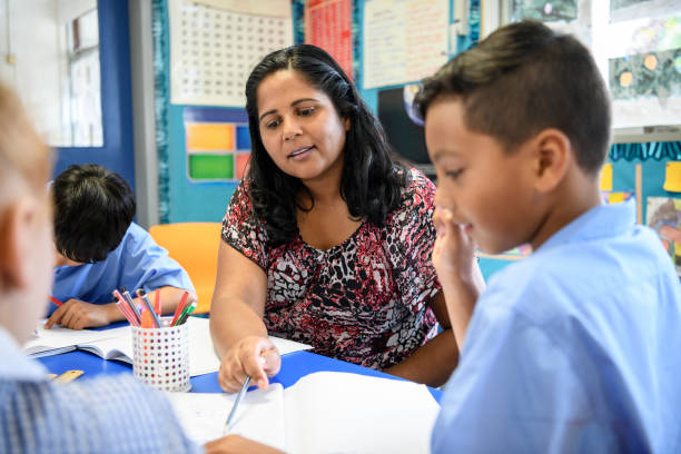aboriginal primary school teacher helping young boy in the classroom - pacific islander ethnicity stock photos and pictures