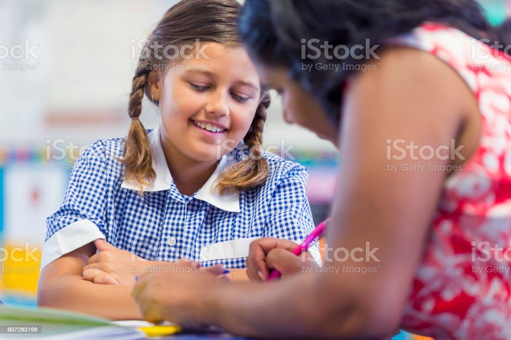 Aboriginal school teacher and aboriginal student working. stock photo