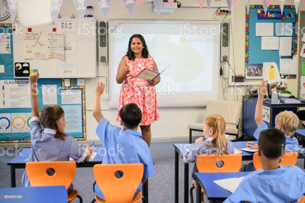 Aboriginal school teacher speaking to class with children raising their hands stock photo
