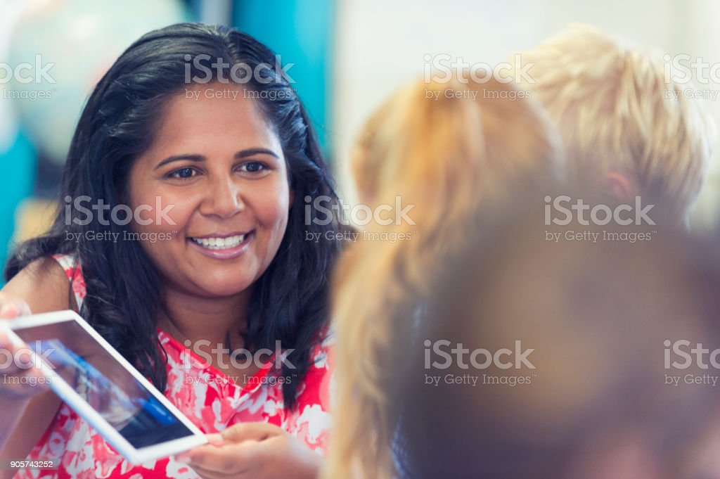 Aboriginal school teacher using digital tablet. She is happy and smiling and showing the children something on the computer. stock photo