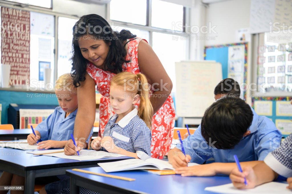 Aboriginal teacher leaning over desk to help young girl with school work stock photo