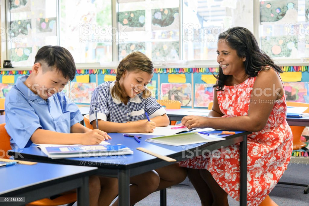 Aboriginal teacher smiling at boy and girl working in classroom stock photo