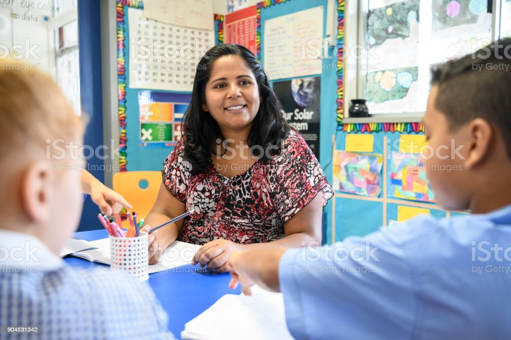 Aboriginal teacher working in primary school and looking at school children stock photo