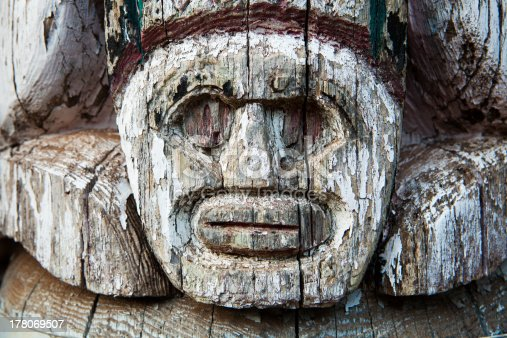 A small detail of a face visible in an old totem pole located at a Boy Scout camp. The wood is cracked and the paint is peeling.