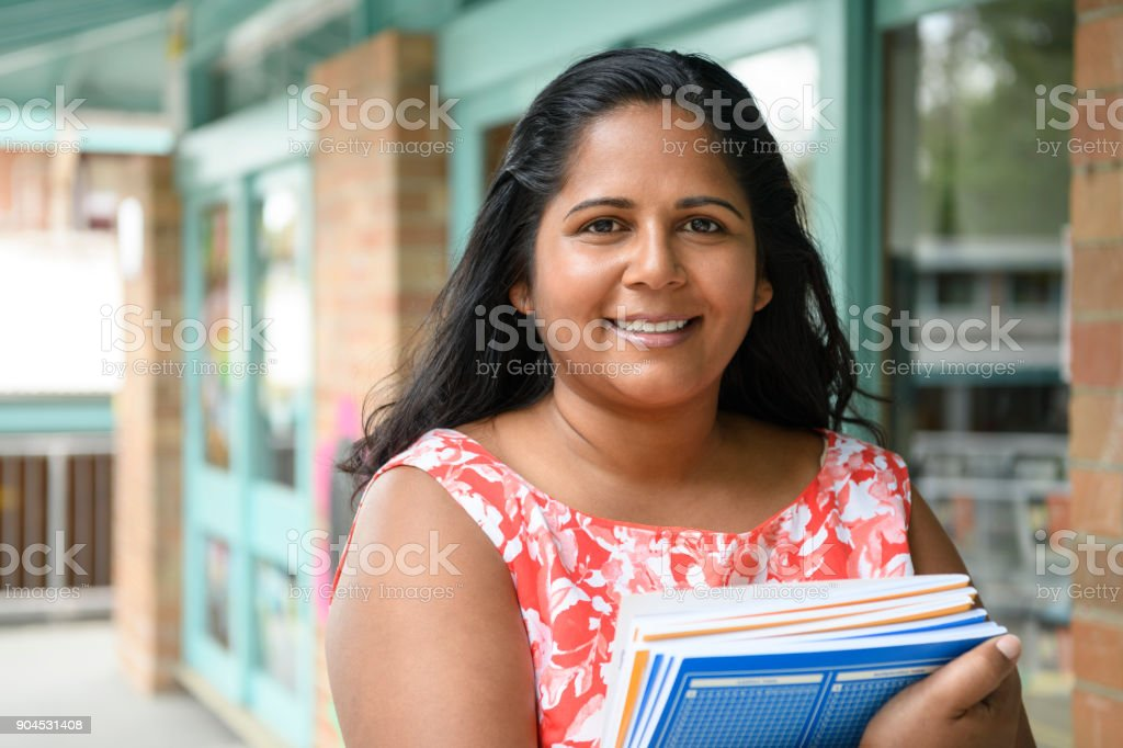 Aboriginal woman holding text books outside school stock photo