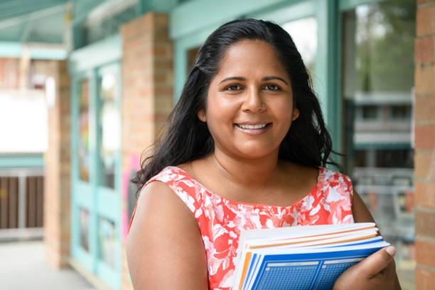 Aboriginal woman holding text books outside school stock photo