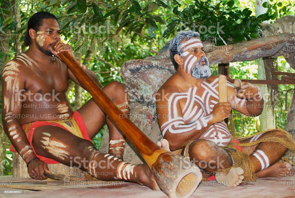 Aborigine actors perform music with traditional instruments in the Tjapukai Culture Park in Kuranda, Queensland, Australia. stock photo