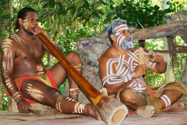 aborigine actors perform music with traditional instruments in the tjapukai culture park in kuranda, queensland, australia. - didgeridoo stock photos and pictures