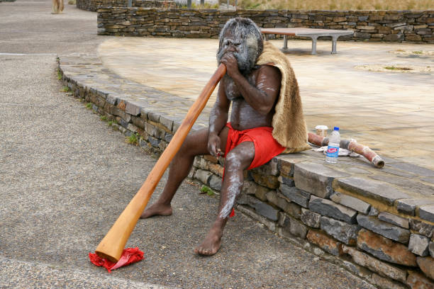 aborigine playing on a didgeridoo. - didgeridoo stock photos and pictures