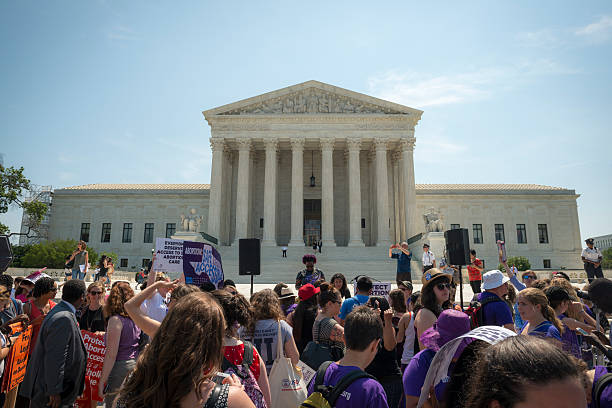 Abortion-rights supporters outside US Supreme Court Washington DC, USA - June 27, 2016: Pro-choice supporters stand in front of the U.S. Supreme Court after the court, in a 5-3 ruling in the case Whole Woman's Health v. Hellerstedt, struck down a Texas abortion access law. pro choice stock pictures, royalty-free photos & images