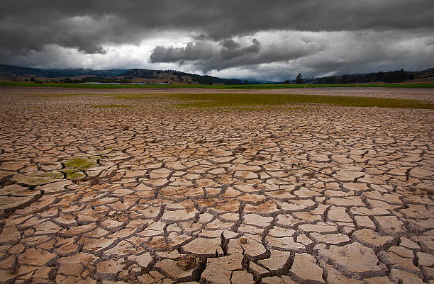 About to rain - Drought Drought land with dense cloudy pattern, apparently rain is about to happen. lake bed stock pictures, royalty-free photos & images