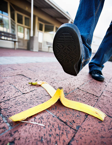 About to step on banana peel in paved shopping complex stock photo