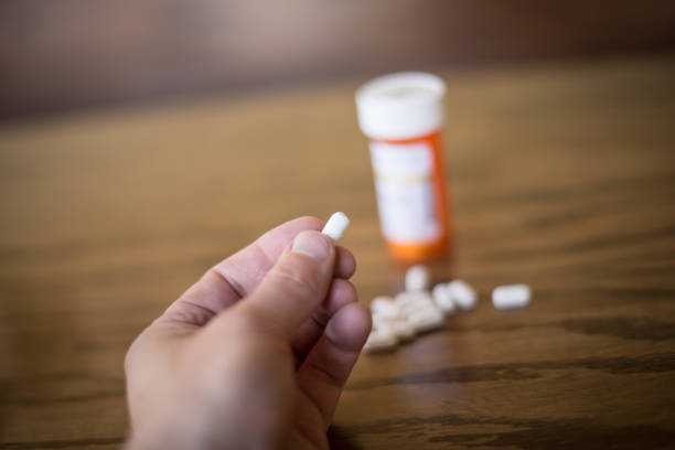 About to Take a Painkiller Close focus shot of hand about to take an opioid painkiller opioid stock pictures, royalty-free photos & images