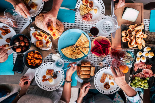 above aerial view of group of friends having fun eating together at lunch or dinner with a table full of different and colorful food and technology mobile phone. mix of hands of caucasian people taking somethings to eat together - foodie stock photos and pictures