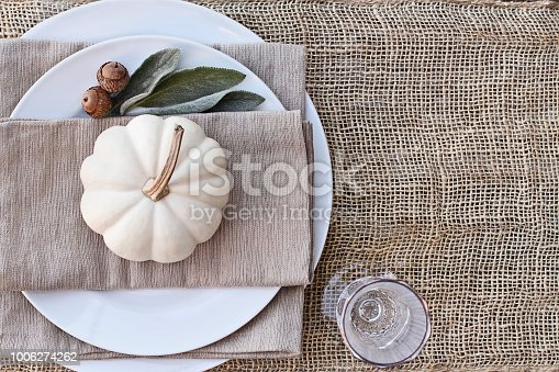 Farmhouse style Thanksgiving Day or Halloween place setting with mini white pumpkins, Lamb's Ears leaves, and acorns over burlap table runner.