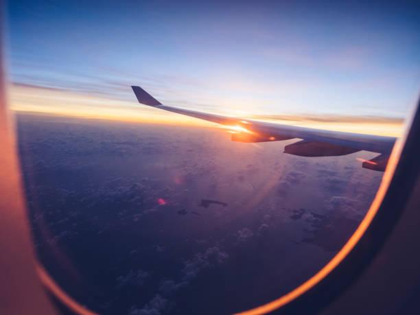 über Wolken mit Flugzeugflügel bei Sonnenuntergang – Foto