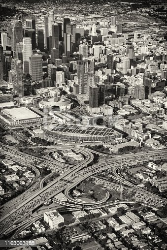 The skyscrapers of downtown Los Angeles, California, just beyond the 10 and 101 interchange during the typical daily rush hour traffic jam in black and white.