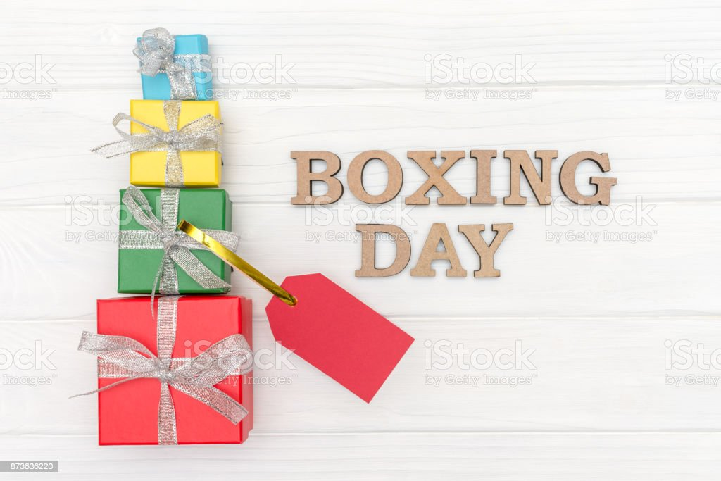 Above gift boxes is tied with a ribbon with words BOXING DAY and red tag on wood white background stock photo