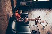 Above high angle view of her she nice attractive focused professional executive director creative designer sitting on couch using device in loft brick industrial style interior work place station.
