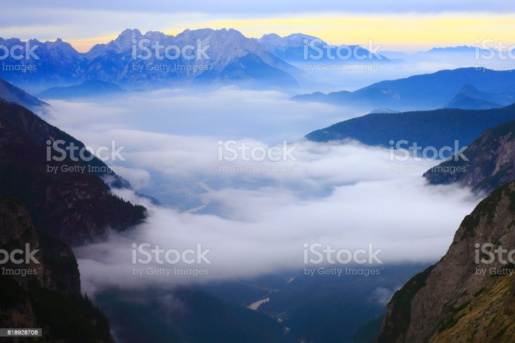 Above Idyllic mist covered Tre Cime di Lavaredo pinnacle and Auronzo di cadore lake, massif mountain range, clouds above Puster valley, dramatic sky at moody dawn, dramatic panorama and majestic Dolomites, Italy tirol alps stock photo