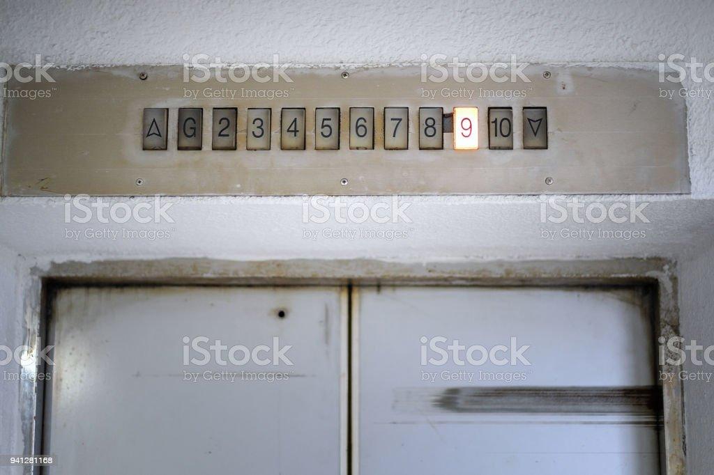 Por encima de la antigua puerta de ascensor luz pantalla con piso número nueve. Interior del ascensor interior. Vista del panel con el número y acero plata. monitor muestra número piso en ascensor - foto de stock