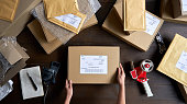 istock Above table top view of female warehouse worker or seller packing ecommerce shipping order box for dispatching, preparing post courier delivery package, dropshipping shipment service concept. 1280366064