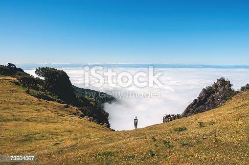 Woman standing on the mountain pasture above the fog, Paul da Serra plateau, Madeira.