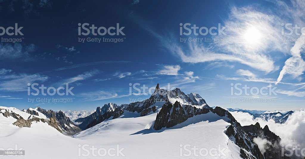Above the clouds snow summit sunburst panorama Alps Italy stock photo