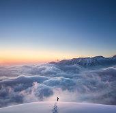 Man hiking through fresh snow above the fog. Idyllic winter mounatin landscape at sunset.