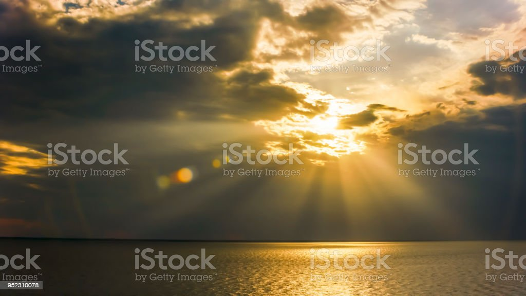 Aerial shot of the sea surface lit by the sun shining through the...