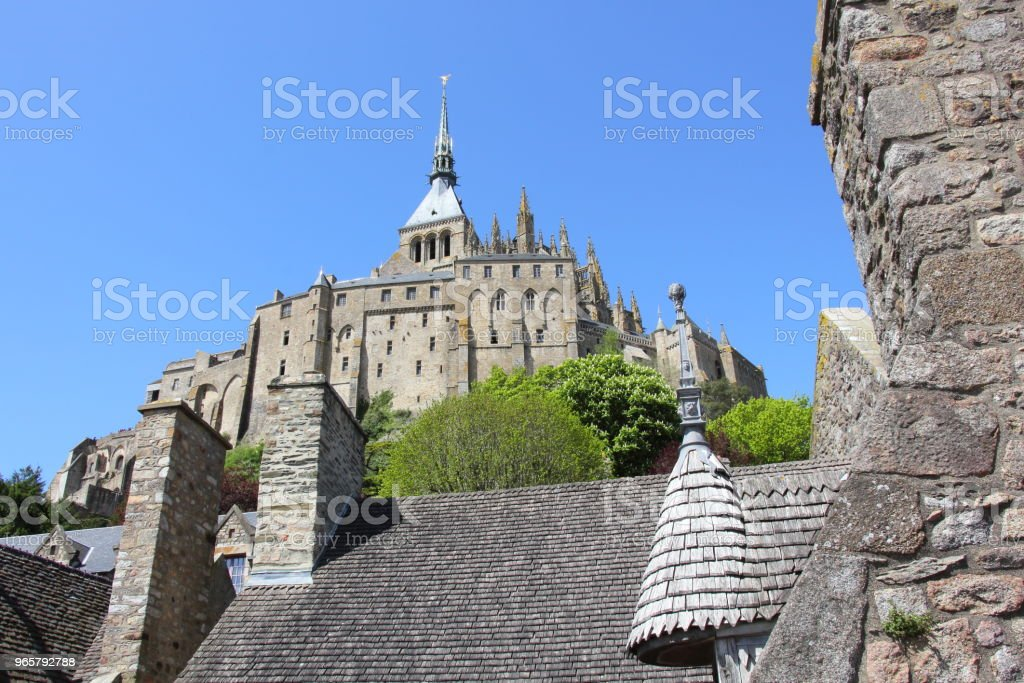 Above the village rooftops, the Mont Saint-Michel Castle - Стоковые фото Аббатство роялти-фри