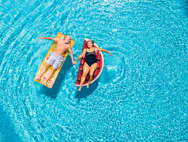 Above vertical view of people old senior couple taking hands with love and having fun on the blue clear swimming pool together enjoying the summer holiday vacation with trendy coloured lilos inflatable mattress stock photo