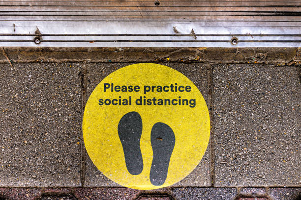 Above view for yellow warning sign to maintain social distance distancing during covid-19 coronavirus outbreak with footsteps on street Above view for yellow warning sign to maintain social distance distancing during covid-19 coronavirus outbreak with footsteps on street covid icon stock pictures, royalty-free photos & images