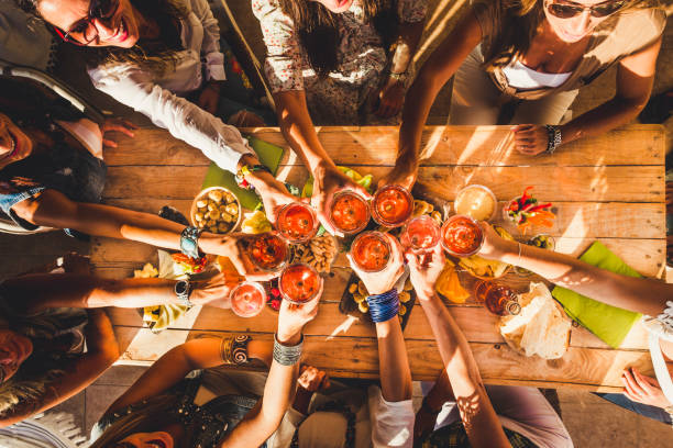 Above view group of friends people enjoy food and drinks toasting and clinking with red wine glasses all together having. fun - celebration and friendship concept - coloured background stock photo