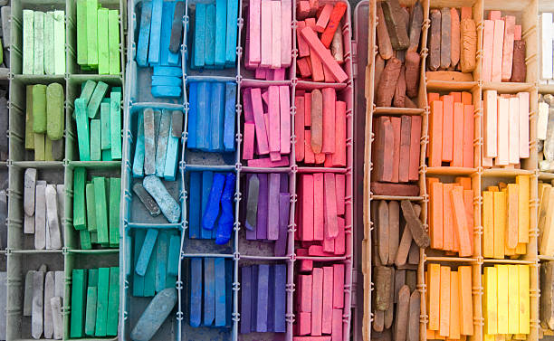 Above view of a divided box filled with a rainbow of pastels stock photo