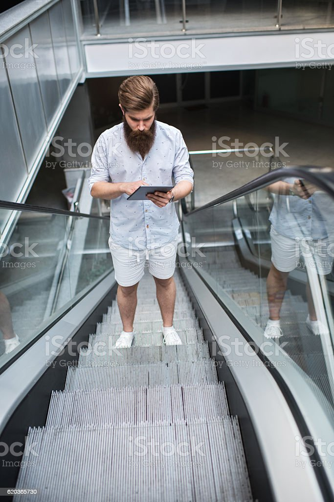 Above view of a man using digital tablet on escalator. foto de stock royalty-free