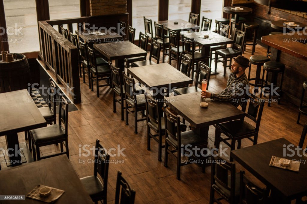 Above view of a man with beer sitting at the table in empty bar. stock photo