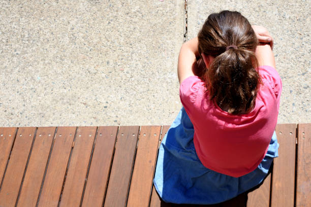 Above view of a sad young girl covering her face and crying in school yard stock photo
