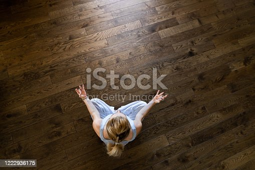 High angle view of a woman doing Yoga exercises in Lotus position on parquet floor at home. Copy space.